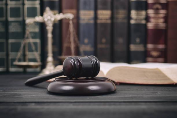 mazo de juez, libros de leyes y escalas de la justicia sobre un fondo negro de madera. - biblioteca de derecho fotografías e imágenes de stock