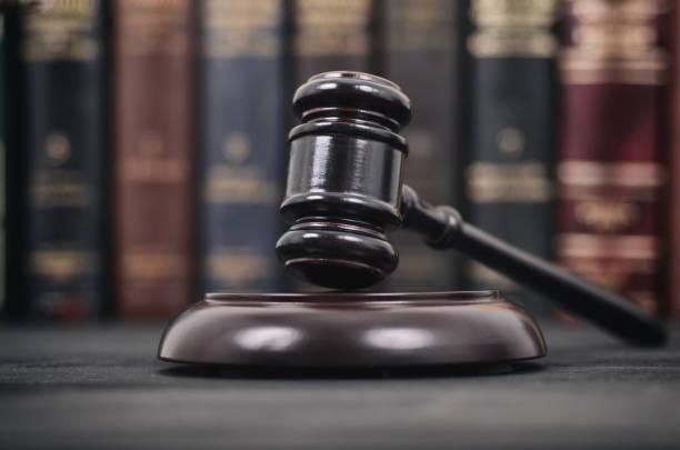 martillo de juez sobre un fondo negro de madera delante de una biblioteca de derecho. - biblioteca de derecho fotografías e imágenes de stock