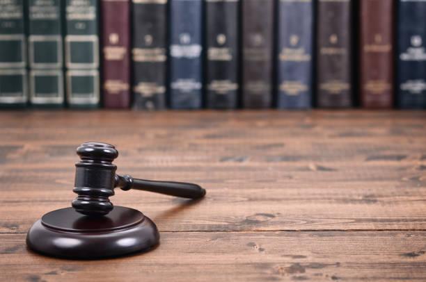 martillo de juez sobre un fondo negro de madera frente a la biblioteca de derecho. - biblioteca de derecho fotografías e imágenes de stock