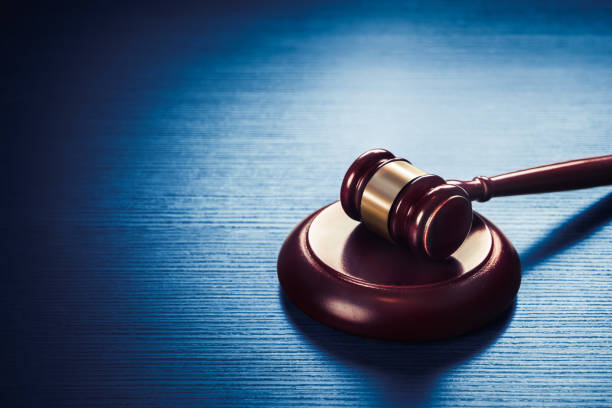 judge gavel on a blue wooden background - innocence stock pictures, royalty-free photos & images