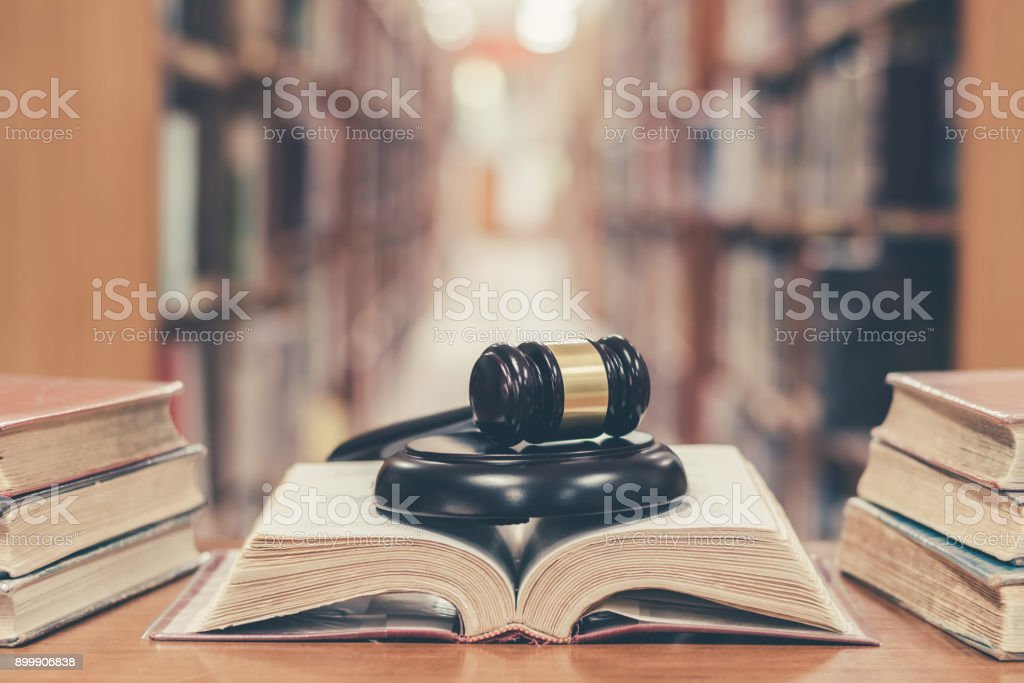Judge gavel on book in library stock photo