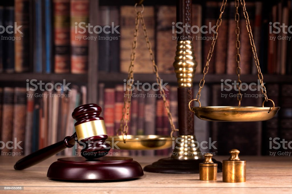 Judge gavel, scales of justice and law books in court stock photo