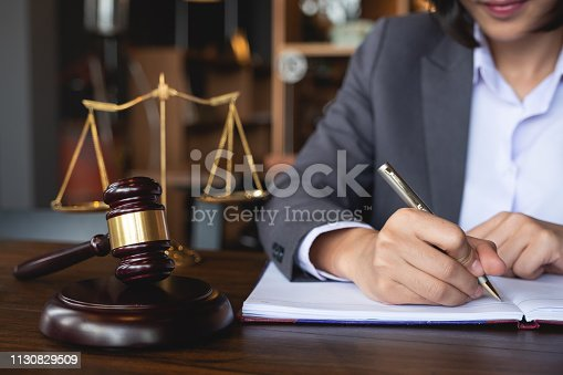 istock Judge gavel with Justice lawyers, Business woman in suit or lawyer working on a documents. Legal law, advice and justice concept. 1130829509