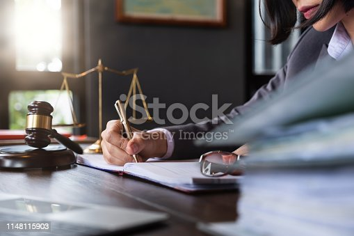 istock Judge gavel with Justice lawyers, Business woman in suit or lawyer working on a documents. Legal law, advice and justice concept. 1148115903
