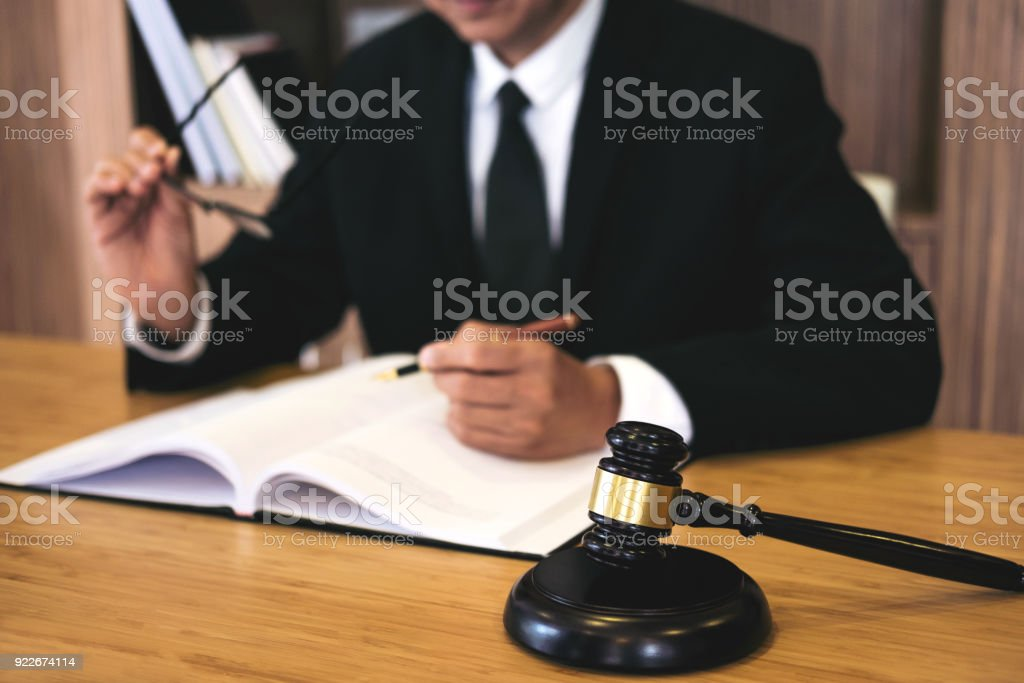 Judge gavel with Justice lawyers, Businessman in suit or lawyer working on a documents. Legal law, advice and justice concept stock photo
