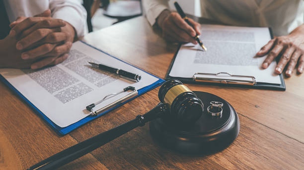 Judge gavel with Justice lawyers deciding, consultation on marriage divorce between married couple and signing divorce documents on table. Concepts of Law and Legal sevices. stock photo