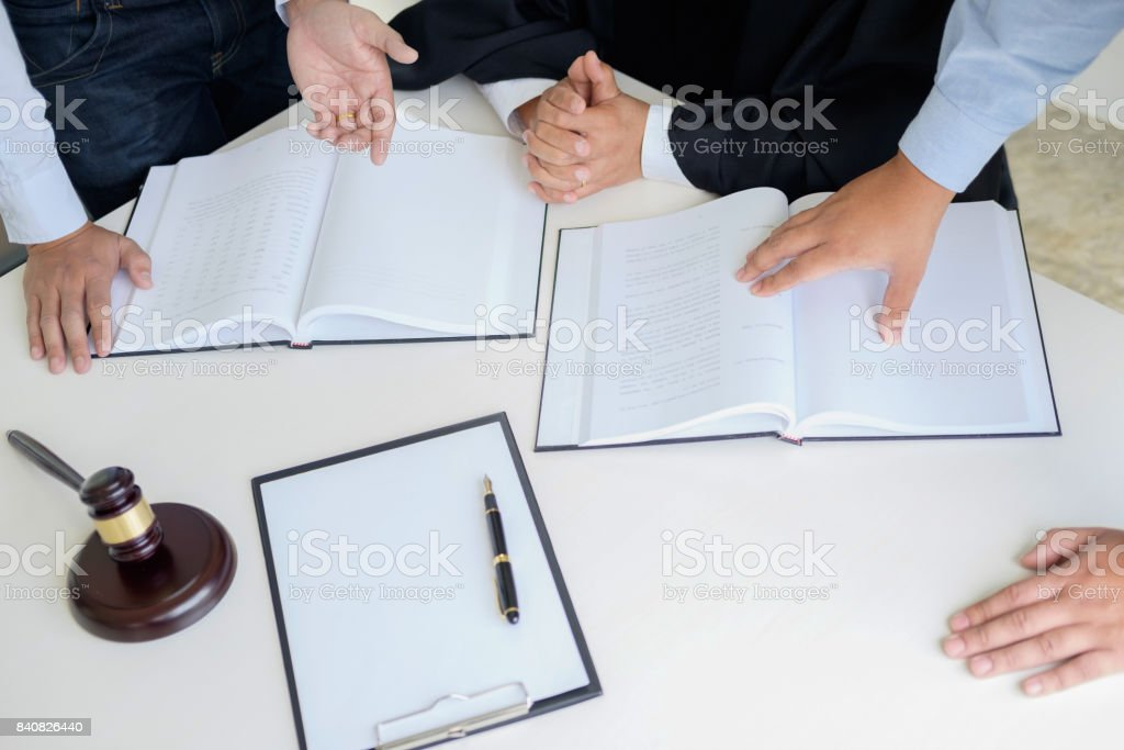 Judge gavel with Justice  lawyers having team meeting at law firm in background. Concepts of law. stock photo