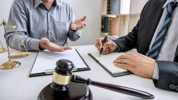 Judge gavel with scales of justice, Businessman and lawyer or counselor consulting and discussing contract papers at law firm in office stock photo