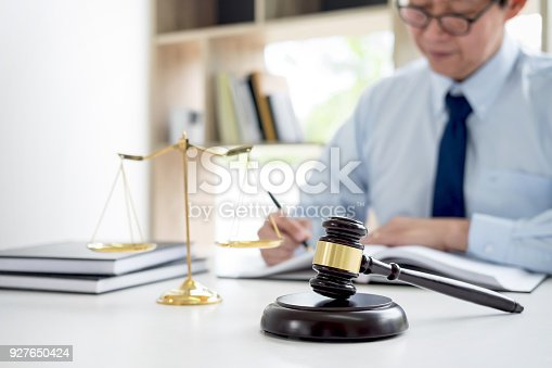 istock Judge gavel with scales of justice, male lawyers working having at law firm in office. Concepts of law 927650424