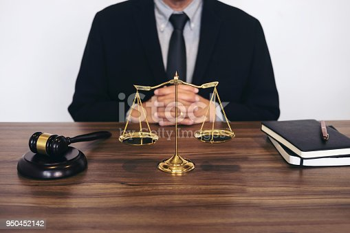 istock Judge gavel with scales of justice, male lawyers working having at law firm in office. Concepts of law 950452142