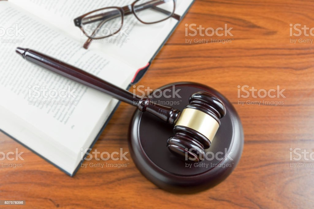 Judge gavel with sound board, open book and glasses on a wooden desk, top view from above, lawyers working place with justice symbols, concept for law and court, copy space stock photo