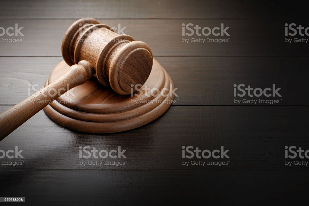 Judge hammer on brown lacquered wooden desk stock photo