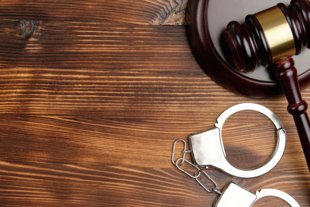 Judge hammer with handcuffs on wooden background with copy space Judge hammer with handcuffs on wooden background with copy space. criminal stock pictures, royalty-free photos & images