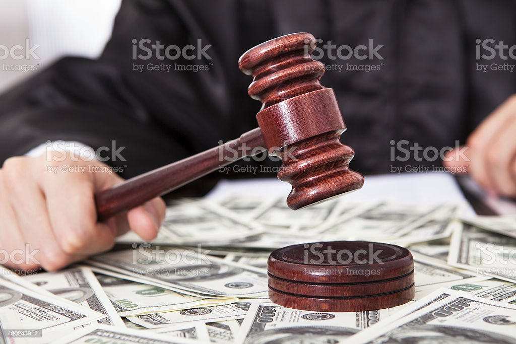 Judge Hitting Mallet On Dollar stock photo