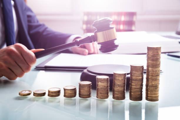 richterin holding mallet in front der gestapelten münzen - wirtschaftsrecht stock-fotos und bilder