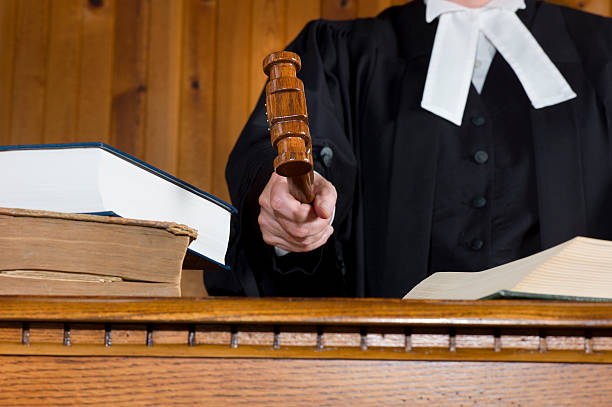 Judge In Traditional Court Robes Using the Gavel. stock photo