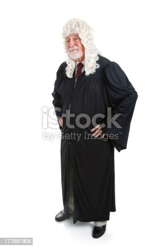 Full body isolated view of a British judge in a wig.