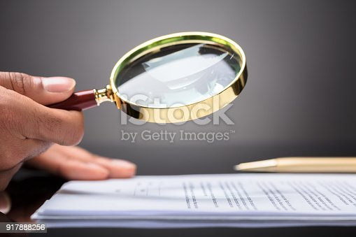 istock Judge Looking At Document With Magnifying Glass 917888256
