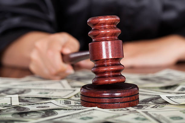 Judge Striking The Gavel Close-up Of Judge Striking The Gavel Surrounded By Banknote lawsuit stock pictures, royalty-free photos & images