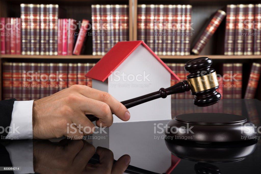Judge With House Model Hitting Gavel stock photo