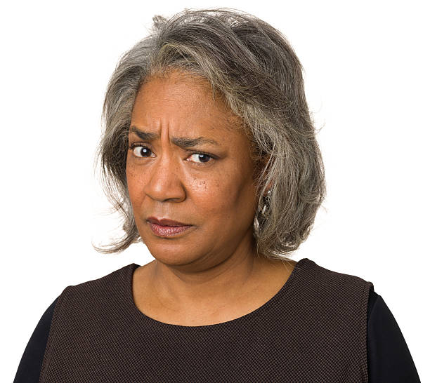 judgemental mature woman frowning at camera - frowning stock photos and pictures