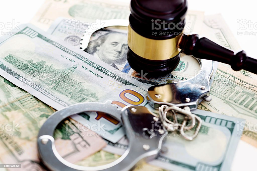 Judges gavel and handcuffs on american dollars stock photo