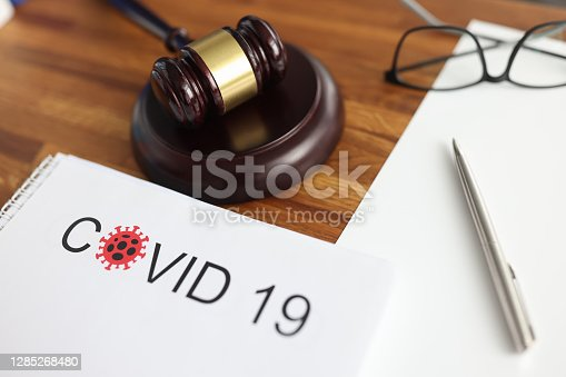 Judges gavel and legal documents lying on table in courthouse closeup. Criminal liability for intentional infection of covid 19 concept.