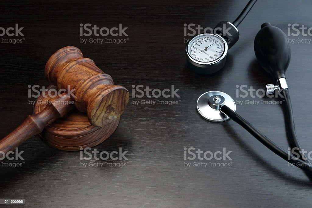 Judges Gavel And Medical Equipment On Black Wooden Background stock photo