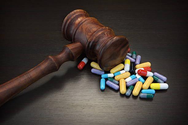 Judges Gavel And Medication On Black Wood Grunge Background stock photo