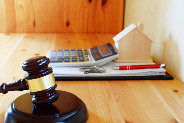 judges gavel and notebook with calculator, house model, keys ans pen on wooden table - real estate law stock photos and pictures