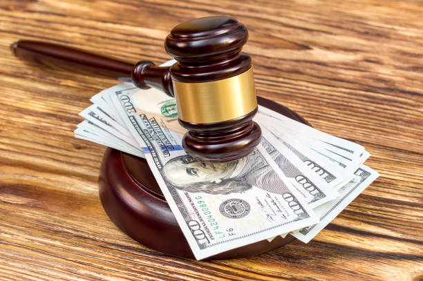 Judge's gavel and stand with US dollar bills on the wooden table. Judge's gavel and stand with US dollar bills on the wooden table. lawsuit stock pictures, royalty-free photos & images