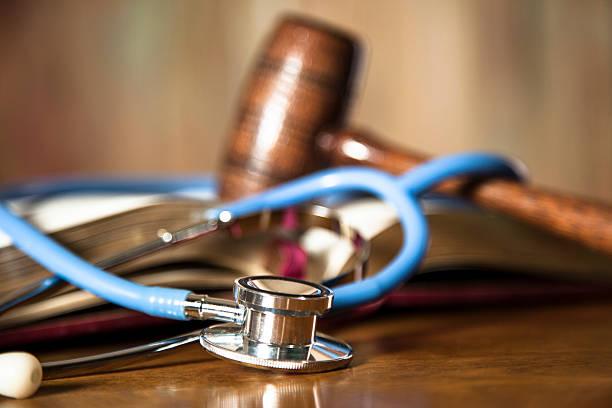judge's gavel and stethoscope on court room table. - legislación fotografías e imágenes de stock