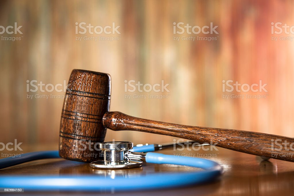 Judge's gavel and stethoscope on court room table. stock photo
