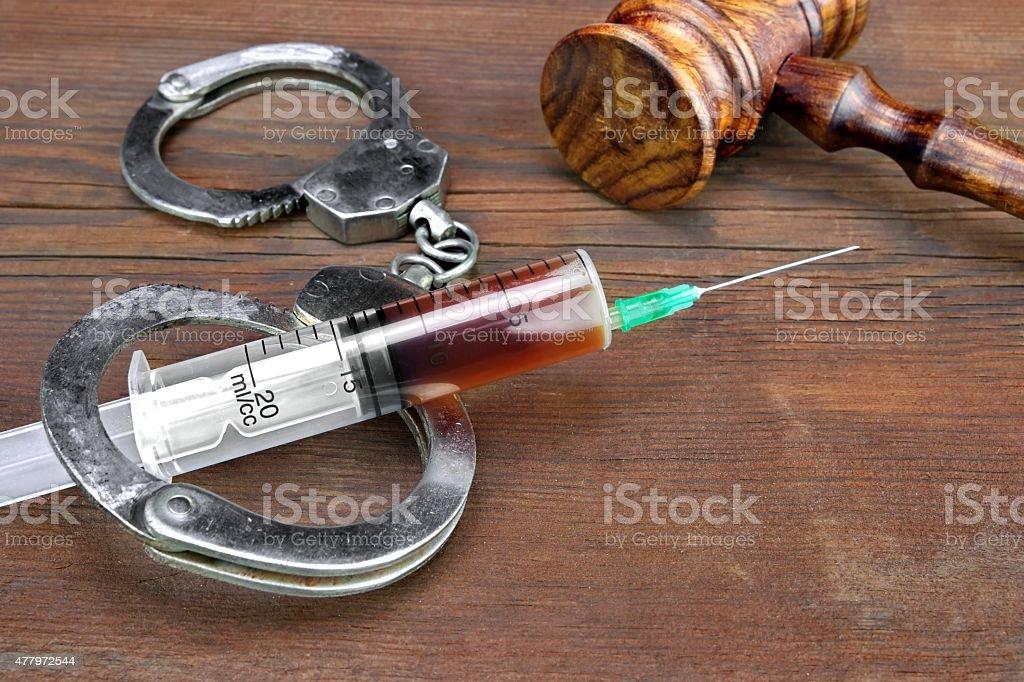 Judges Gavel And Syringe On Wood Rough Background Close-up Of Judges Gavel And Syringe  With Injection On The Brown Wood Rough Background 2015 Stock Photo