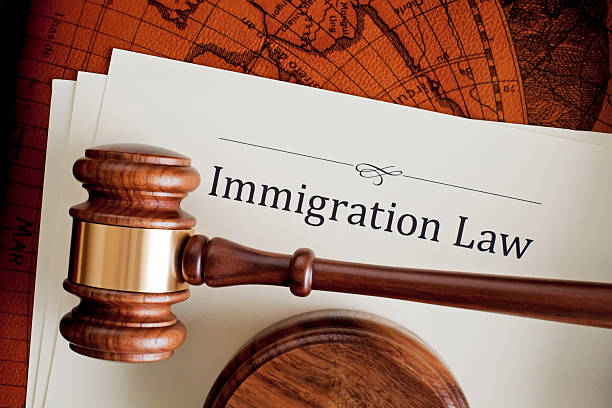 Judge's gavel atop an immigration law paper stock photo