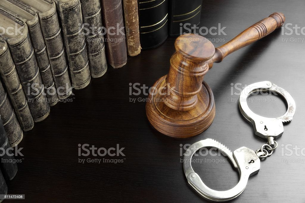 Judges Gavel, Handcuffs And Old Book On The Black Table stock photo