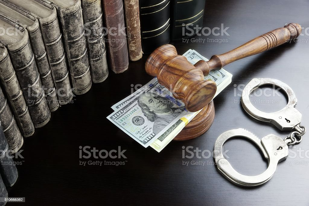 Judges Gavel, Handcuffs, Dollar Cash And Book On  Black Table stock photo