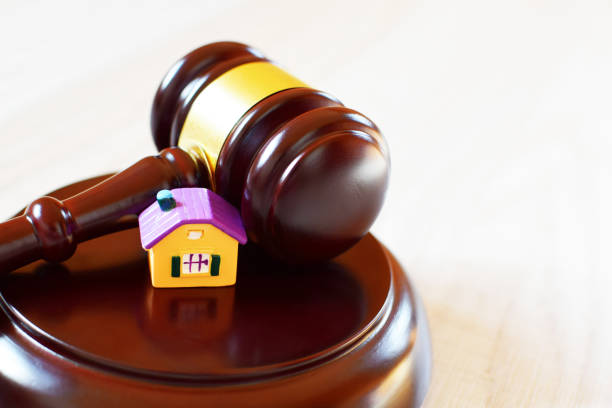 judges gavel laying on sound block next to yellow house - real estate law stock photos and pictures