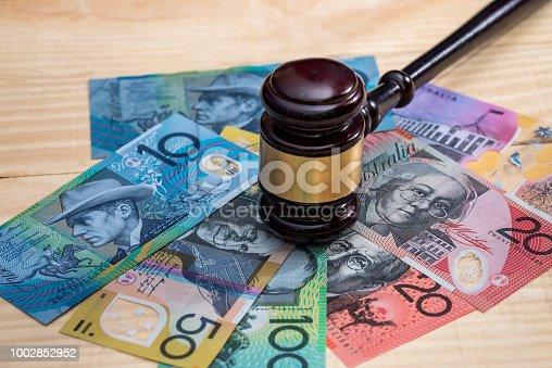 Judge's gavel on australian dollar banknotes, closeup