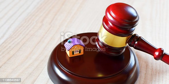 istock Judges gavel on sound block next to yellow colorful house model 1138540597