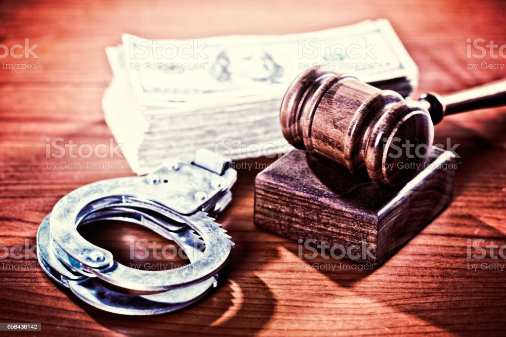 Judge's gavel on wooden rest with money and handcuffs stock photo
