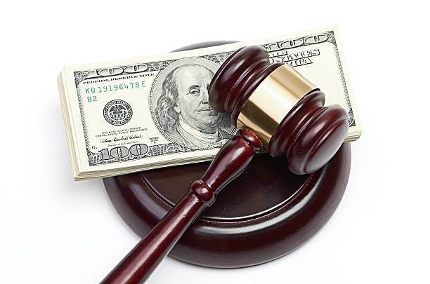 judge's gavel sitting on a stack of american money - judge sports official stock photos and pictures