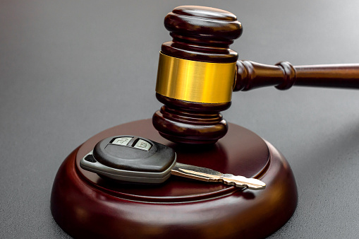Judge's gavel with car key on black. Car auction and insurance concept.