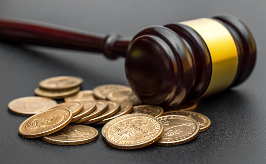 182148217 istock photo Judge's gavel with coins on black. 1212580658