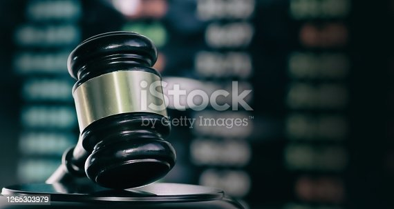 Judges gavel with glowing computer screen monitor background.