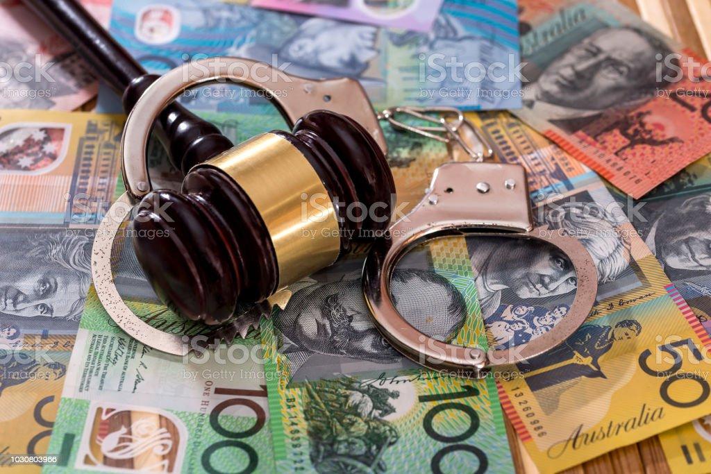 Judge's gavel with handcuffs on australian dollars stock photo