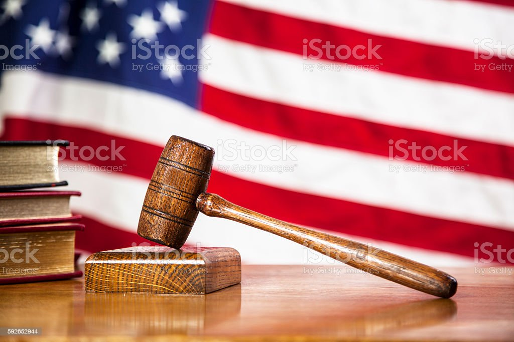 Judge's gavel with USA flag on court room table. stock photo