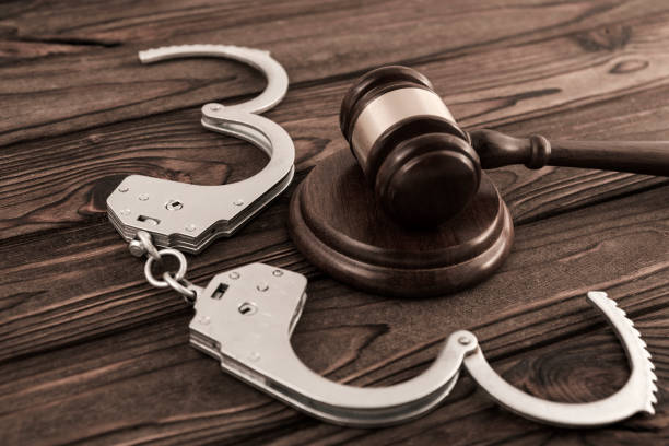 Judge's hammer, iron handcuffs for arresting criminals on wooden background. stock photo