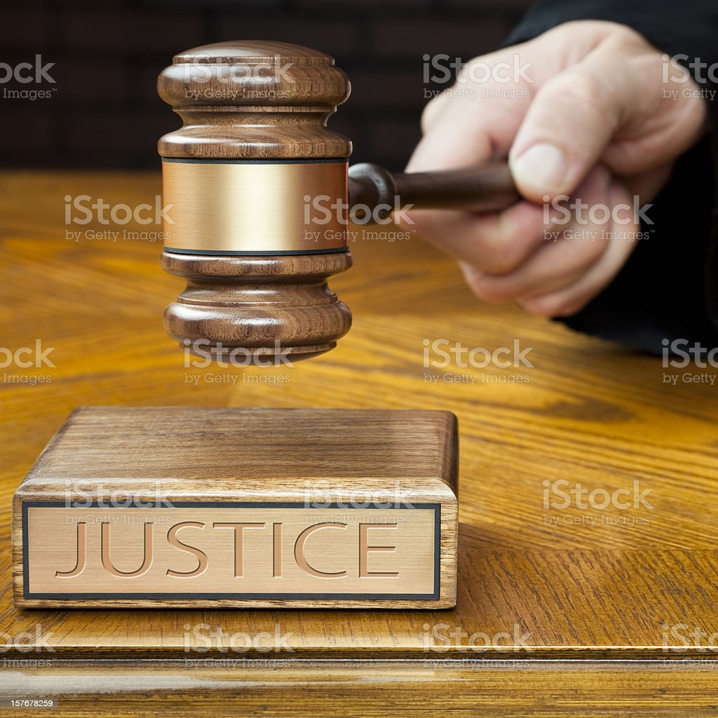 Judge's Hand Pounding Gavel To Administer Justice stock photo