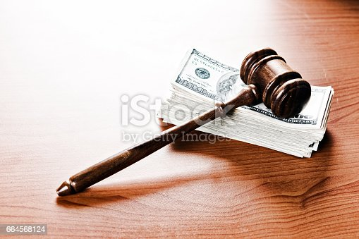 A judge's or auctioneer's gavel acts as a paperweight on a thick stack of banknotes. Payment, a fine, or bribery?